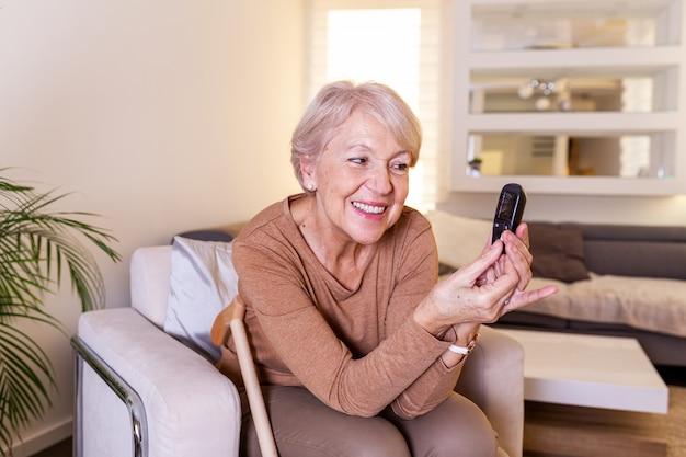 Starsza kobieta testuje na wysoki poziom cukru we krwi. kobieta trzyma urządzenia do pomiaru cukru we krwi. kobieta robi badanie cukru we krwi. kobieta sprawdza poziom cukru we krwi glukometrem i paskiem testowym w domu