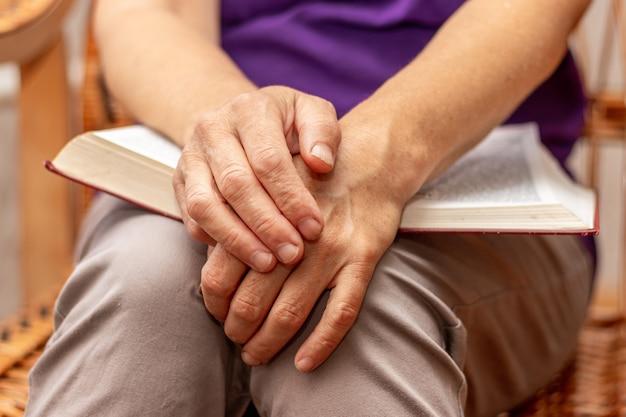 Starsza kobieta trzyma biblię na kolanach i modli się po przeczytaniu biblii