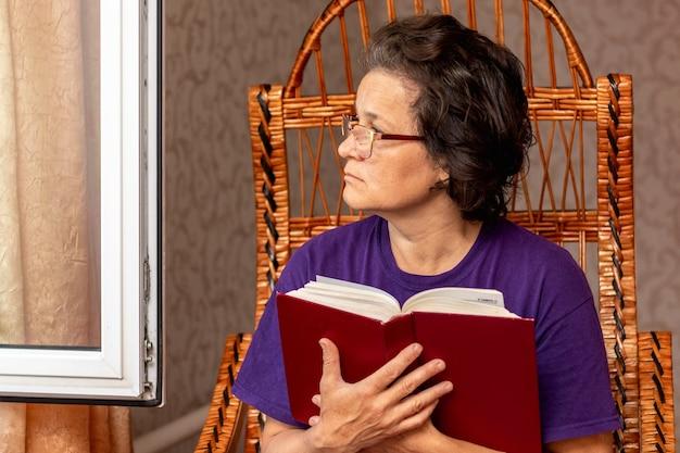 Starsza kobieta trzyma biblię w dłoni i wygląda przez otwarte okno, rozmyślając nad tym, co przeczytała