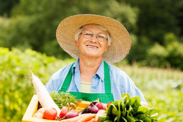 Starsza kobieta trzyma drewniane pudełko z warzywami