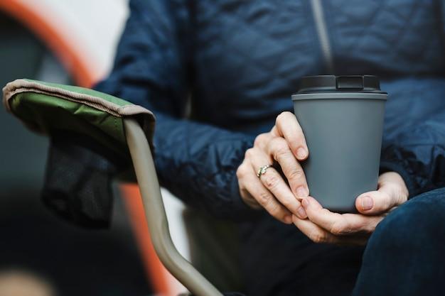 Starsza kobieta trzyma kubek wielokrotnego użytku