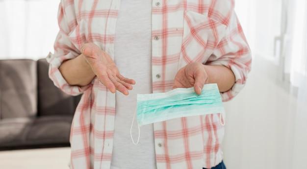 Starsza kobieta trzyma medyczną maskę