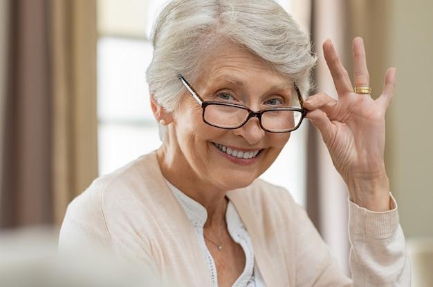 Starsza kobieta trzyma okulary
