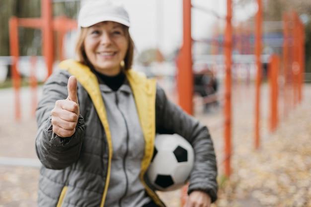 Starsza kobieta trzyma piłkę nożną i daje kciuki do góry podczas ćwiczeń