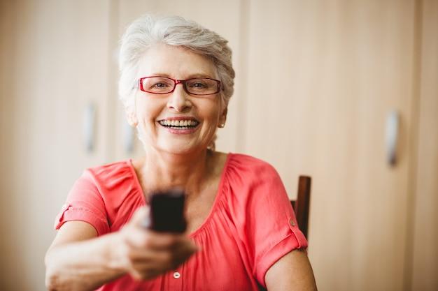 Starsza kobieta trzyma pilot do tv