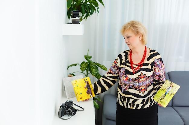 Starsza kobieta trzyma płótno ze zdjęciem swoich wnuków