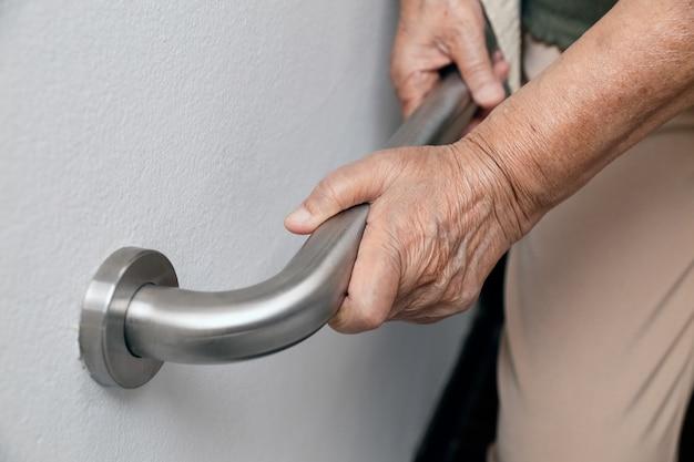 Starsza kobieta trzyma poręcz dla bezpiecznych kroków spaceru