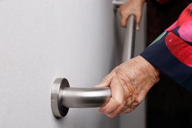 Starsza kobieta trzyma poręcz dla kroków bezpieczeństwa