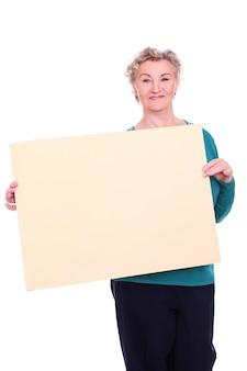 Starsza kobieta trzyma pusty znak