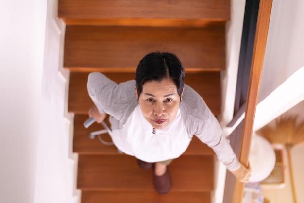 Starsza kobieta trzyma się za ręce trzymając kije podczas chodzenia po schodach w domu