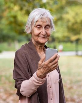 Starsza kobieta trzyma smartfona