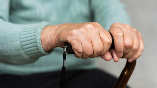 Starsza kobieta trzyma w rękach laskę