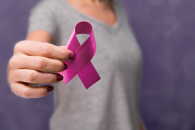 Starsza kobieta trzyma w świadomości fioletowy wstążka miejsca kopiowania. symbol służy do zwiększania świadomości na temat choroby alzheimera, przemocy wobec osób starszych, epilepsji, raka trzustki, raka tarczycy i tocznia. ścieśniać.