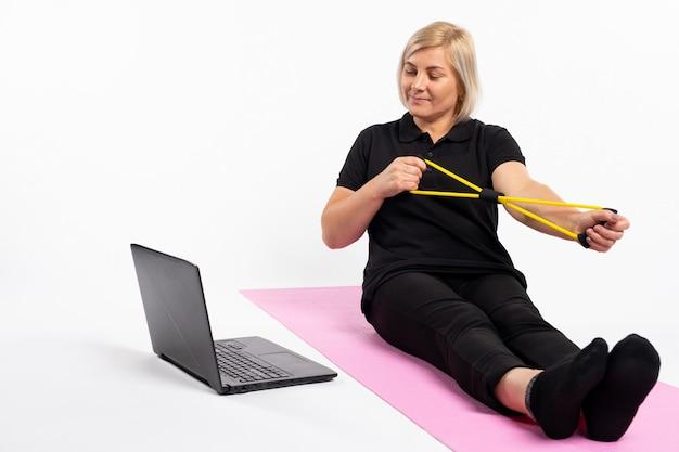 Starsza kobieta trzyma zespół oporu przed laptopem