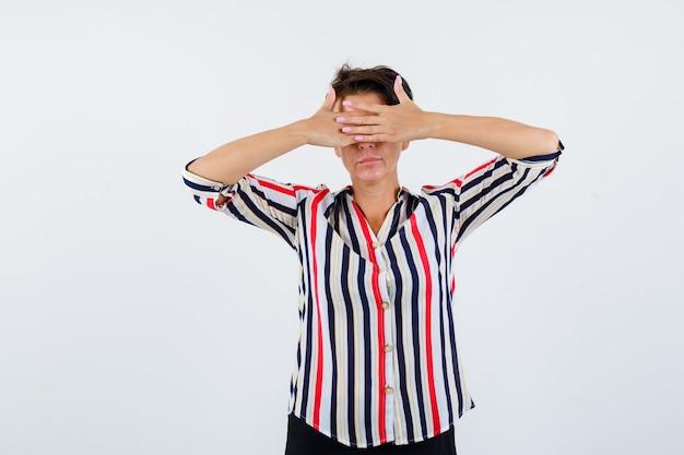 Starsza kobieta trzymając się za ręce na oczach w pasiastej koszuli i patrząc spokojnie, widok z przodu.