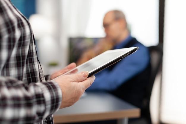 Starsza kobieta trzymająca komputer typu tablet w pozycji stojącej