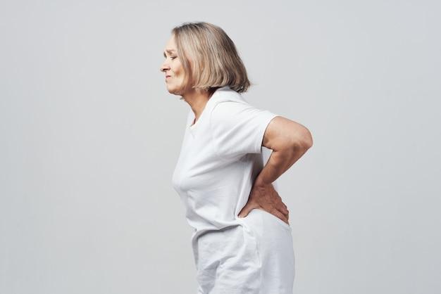 Starsza kobieta trzymająca leczenie bólu w dolnej części pleców