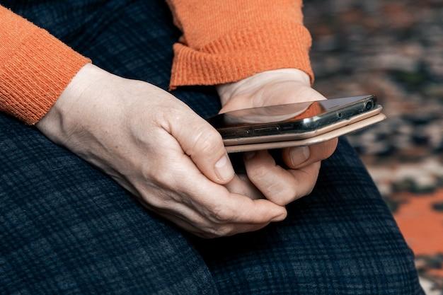 Starsza kobieta trzymająca telefon komórkowy, komunikująca się przez internet