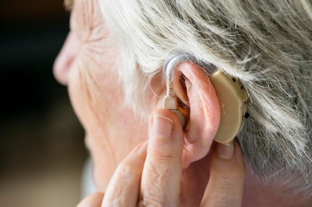 Starsza kobieta ubrana w aparat słuchowy