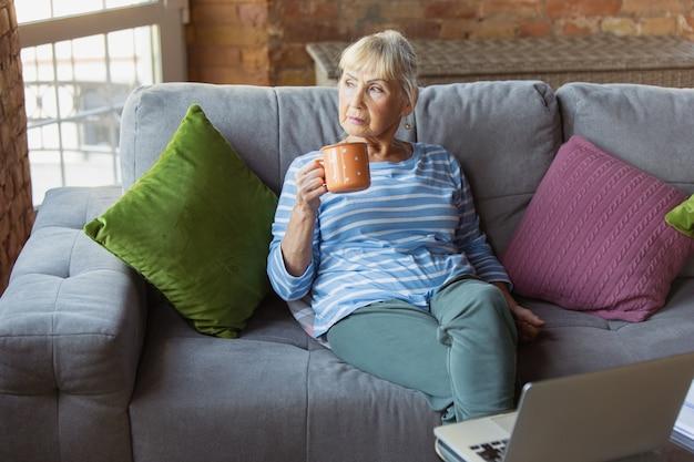 Starsza kobieta ucząca się w domu, pobierająca kursy online