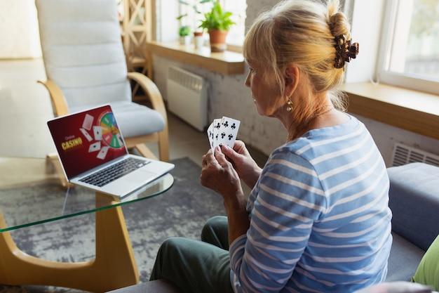 Starsza kobieta uczy się w domu i korzysta z kursów online