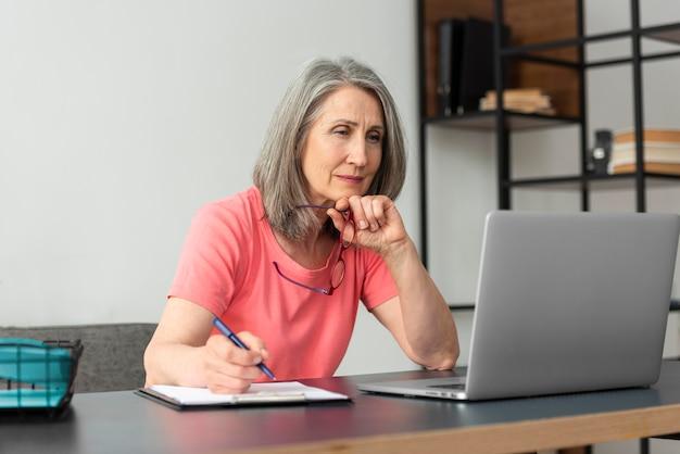 Starsza kobieta uczy się w domu podczas korzystania z laptopa i robienia notatek