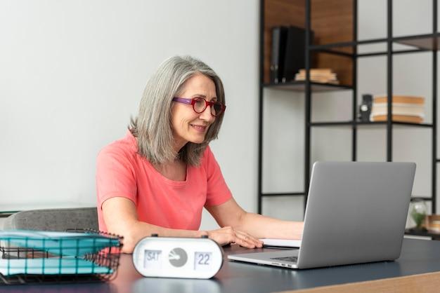 Starsza kobieta uczy się w domu podczas korzystania z laptopa