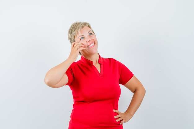 Starsza kobieta udając rozmowę na telefon komórkowy w czerwonej koszulce i patrząc zadowolony.