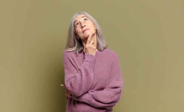 Starsza kobieta uśmiecha się radośnie i marzy lub wątpi