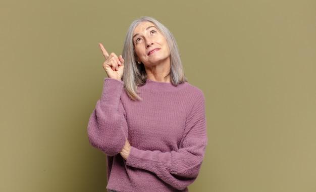 Starsza kobieta uśmiecha się radośnie i patrzy w bok, zastanawiając się, myśląc lub mając pomysł