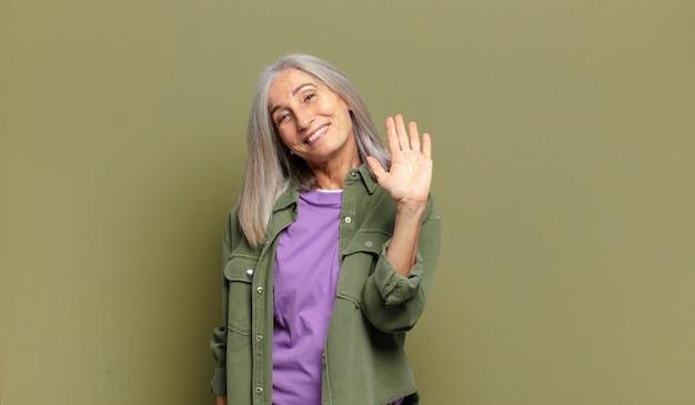 Starsza kobieta uśmiecha się radośnie i wesoło, macha ręką, wita i wita lub żegna się