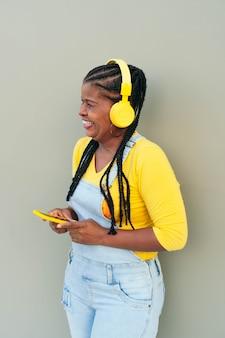 Starsza kobieta uśmiechając się stojąc na ulicy. czarna kobieta słuchania muzyki na smartfonie na zewnątrz.