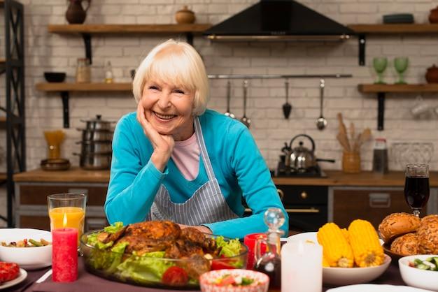 Starsza kobieta uśmiechnięta i patrzeje kamerę