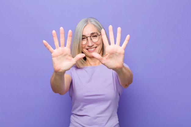 Starsza kobieta uśmiechnięta i patrzeje życzliwa, pokazuje liczbę dziesięć lub dziesiąta z ręką do przodu, odliczanie