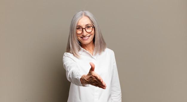 Starsza kobieta uśmiechnięta, wyglądająca na szczęśliwą, pewną siebie i przyjazną, oferująca uścisk dłoni w celu zawarcia transakcji, współpracująca