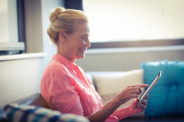 Starsza kobieta używa cyfrową pastylkę