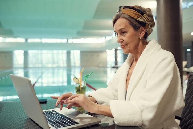 Starsza kobieta używa laptop w zdroju kurorcie