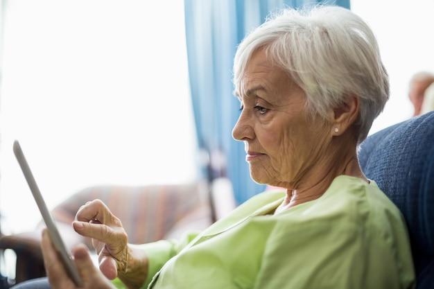 Starsza kobieta używa pastylkę