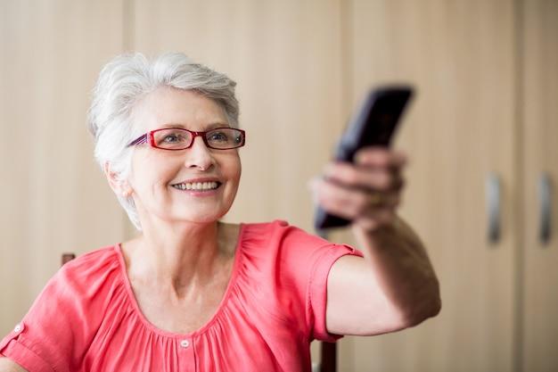 Starsza kobieta używa pilot do tv