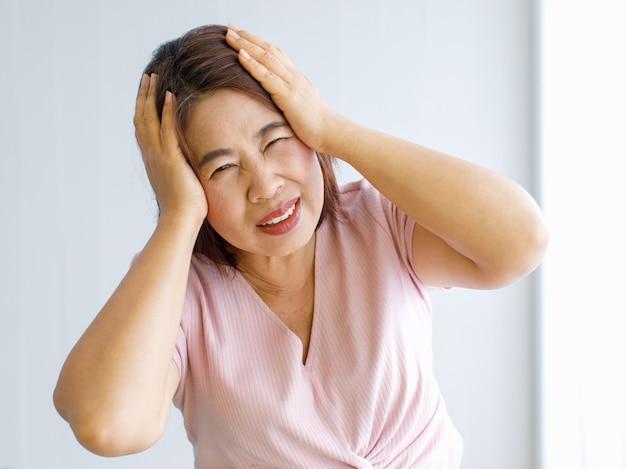 Starsza kobieta używa rąk do chwytania i trzymania głowy z bólem i cierpi na wykrzywioną twarz z powodu bólu głowy z chorobą naczyń mózgowych lub udarem głowy.