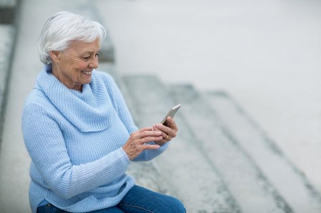 Starsza kobieta używa telefon komórkowego