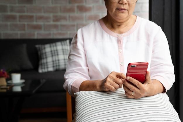 Starsza kobieta używa telefonu komórkowego białego obsiadanie na kanapie w domu