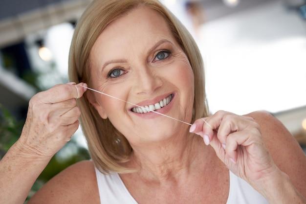 Starsza kobieta używająca nici dentystycznej w łazience