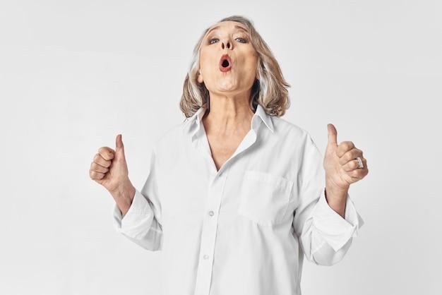 Starsza kobieta w białej koszuli emocje jasnym tle