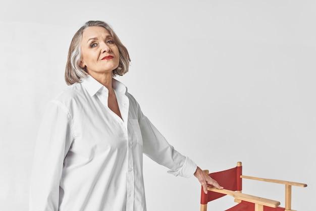 Starsza kobieta w białej koszuli siedzi na krześle zbliżenie stylu życia