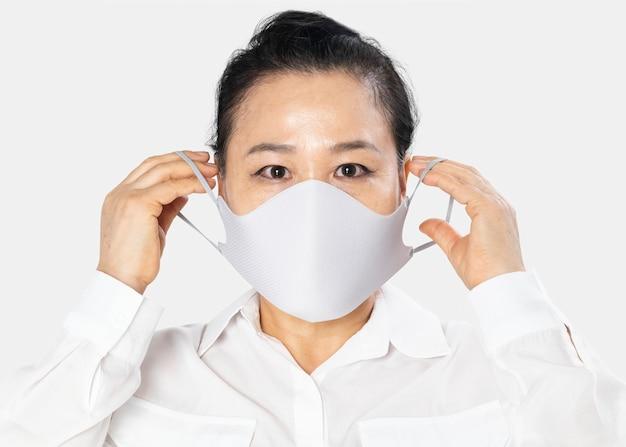 Starsza kobieta w białej masce na twarz kampania covid-19 z przestrzenią projektową