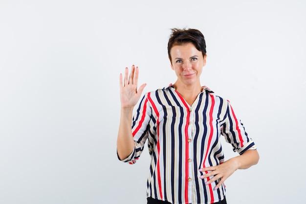 Starsza kobieta w bluzce w paski pokazując znak stopu, trzymając rękę na talii i wyglądający na pływającego, widok z przodu.
