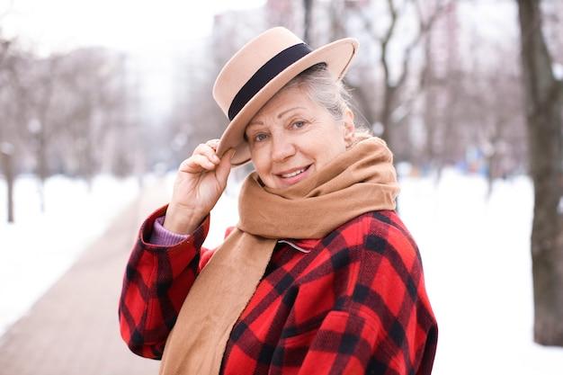 Starsza kobieta w ciepłych ubraniach na zewnątrz. ferie zimowe
