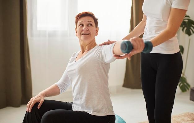 Starsza kobieta w covid recovery robi ćwiczenia z pielęgniarką i hantlami
