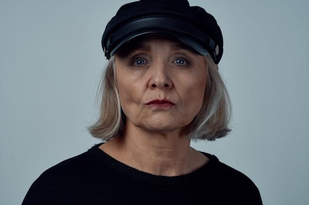Starsza kobieta w czarnym kapeluszu moda zbliżenie jasnym tle